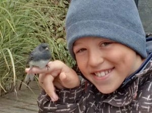 Rowan Maury holding  junco after window collision