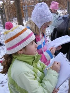 A group of children sketching in their nature journals - Photo by Drew Monkman